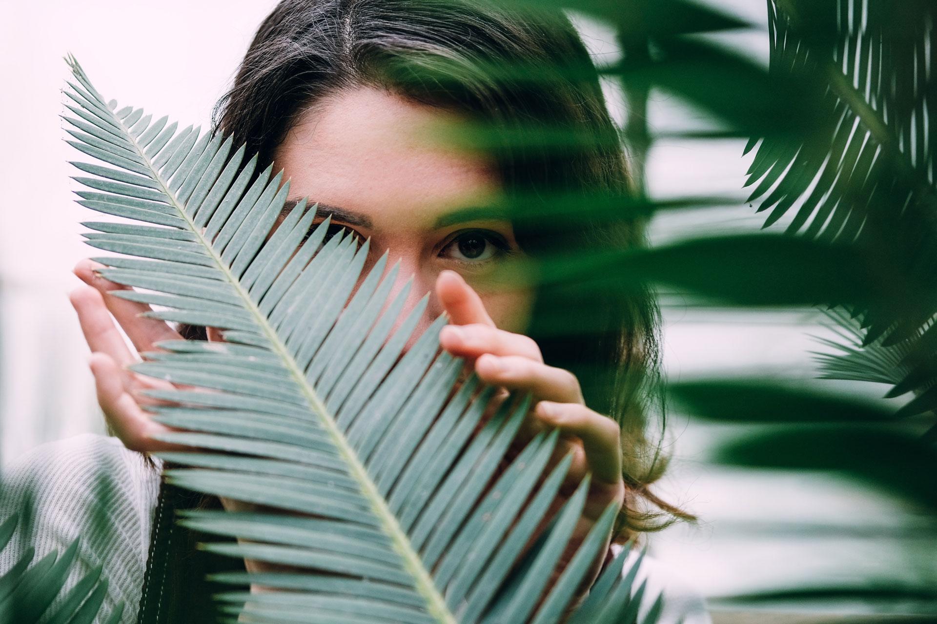Mulher jovem com cara escondida por folha de palmeira